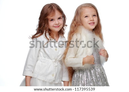 Two beautiful little girl in adorable white dresses isolated on white background/Joyful kids as Christmas princesses