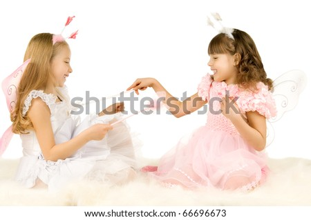 two beautiful  little girl with wings, sit and  fun game, smile,  on white background, isolated