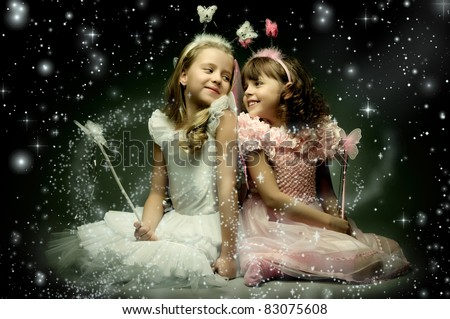 two beautiful  little girl with wings, sit and  smile on dark starry sky background