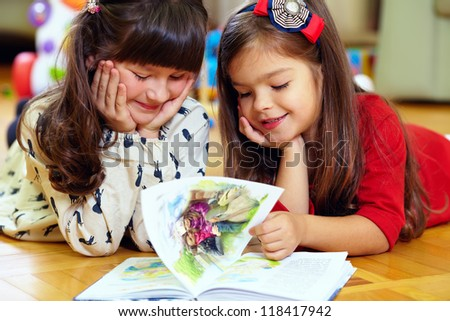 two beautiful little girls reading book at home