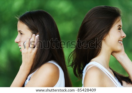 two beautiful long-haired woman profile standing behind each talk phone