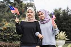 Two beautiful malay girls holding Malaysian flag at a public park
