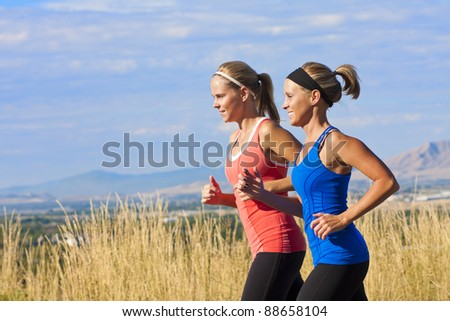 Two beautiful middle-aged female joggers training for a marathon