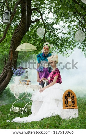 Two beautiful romantic women on a picnic in a fairy foggy  forest. Outdoors.