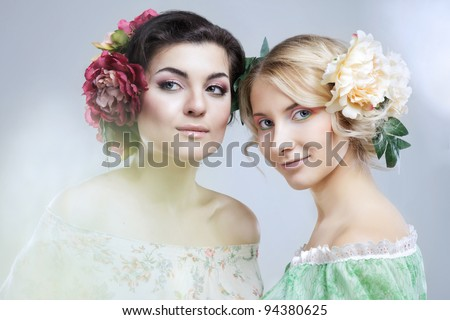 two beautiful sensual women with flowers in hair