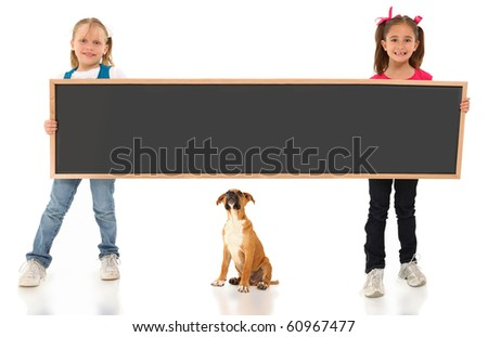 Two beautiful seven year old girls holding giant chalk board with boxer puppy friend over white background.