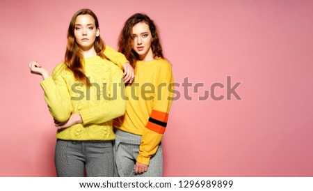 Two beautiful sexy smiling gorgeous girls looking at camera. Hot women standing in stylish yellow sweaters, on pink background. Studio shot. Isolate