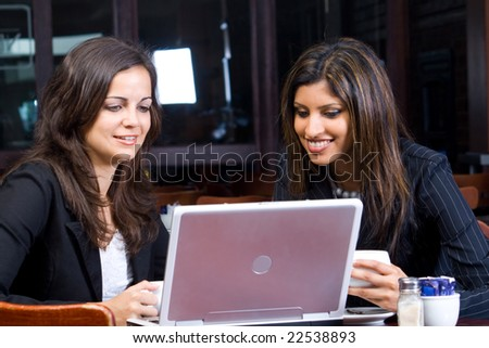 two beautiful smiling businesswomen in cafe with laptop and papers