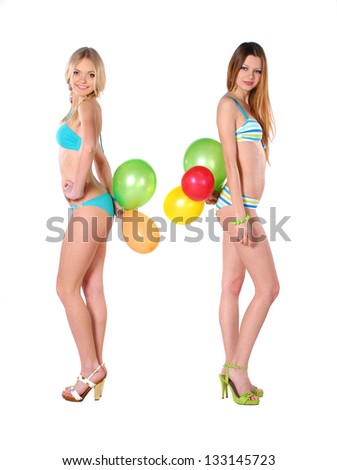 Two beautiful smiling girl in bikini with baloons