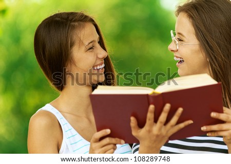 Two beautiful smiling girls reading book, against green of summer park.