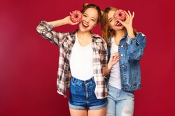 Two beautiful smiling hipster girls posing in trendy summer checkered shirt clothes.Women isolated on red background.Positive models covering eyes by pink donuts with powder