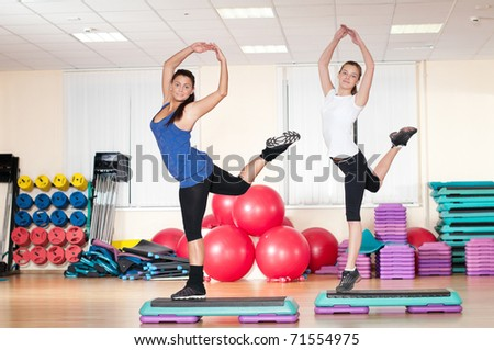 Two beautiful sport woman doing stretching fitness exercise at sport gym. Step.