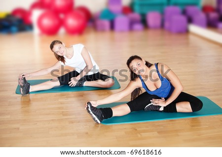 Two beautiful sport woman doing stretching fitness exercise at sport gym. Yoga