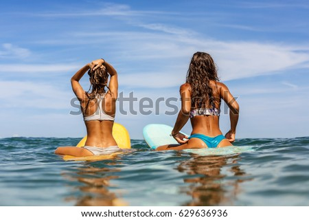Stock Photo Two beautiful sporty surfing girl in sexy bikini sit on a big longboard surf surfboard board and wait for big wave on sunrise or sunset in the ocean. Modern active sport lifestyle and summer vacation.