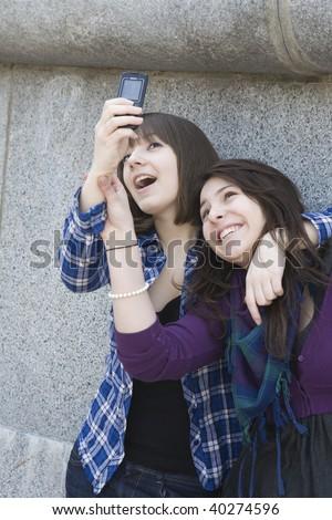 Two beautiful teen girls n taking self portraits  by mobile phone - stock photo