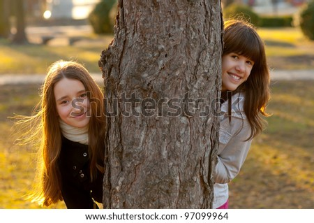 Two beautiful teenage girls having fun in the park on sunny spring day.