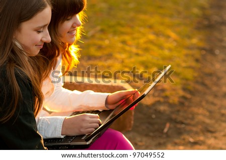 Two beautiful teenage girls having fun with notebook in the park on sunny spring day.