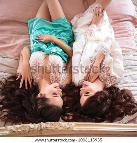 Two beautiful twins young women in a lacy sleepwear. Bride and braidsmaid together in a morning. #1006115935