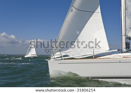 Two beautiful white yachts sailing on a bright sunny day