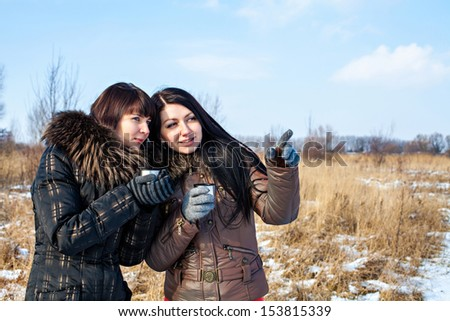 Two beautiful woman friends dressed in winter clothes enjoying a conversation, drinking hot drink and laughing together outdoors
