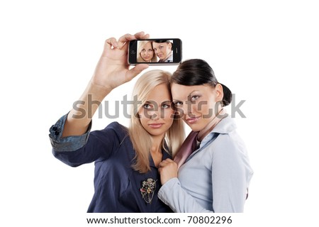 two beautiful woman in formal dress looking at a smart phone and taking photo