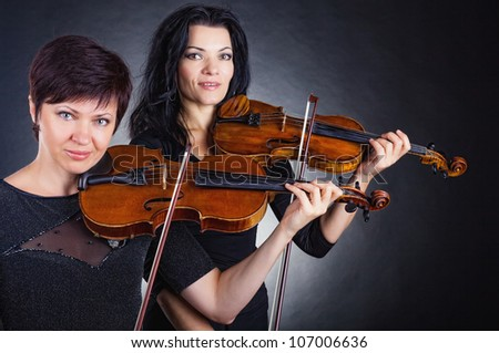 Two beautiful woman playing the violin on dark background