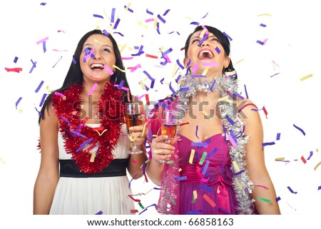 Two beautiful women celebrate new year party with champagne and confetti and laughing together