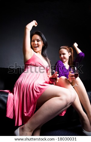 Two beautiful women dancing and drinking wine during a party