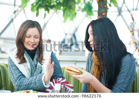 Two beautiful women drinking coffee, having lunch and chatting at cafe