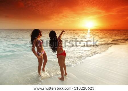 Two beautiful women in bikini enjoying sunset on beach