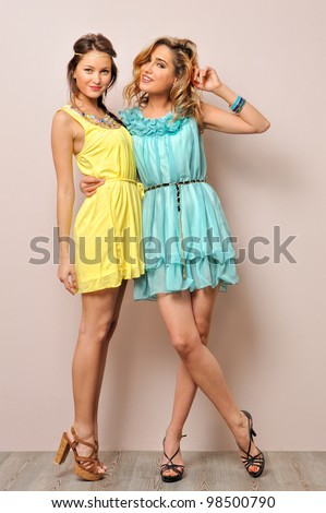 Two beautiful women in summer dresses. Studio  portrait.