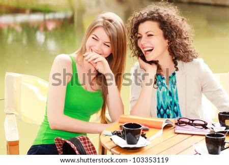 Two beautiful women laughing over a coffee at the river side terrace - vibrat summer colors