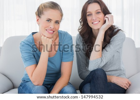 Two beautiful women posing while sitting on the couch and looking at camera