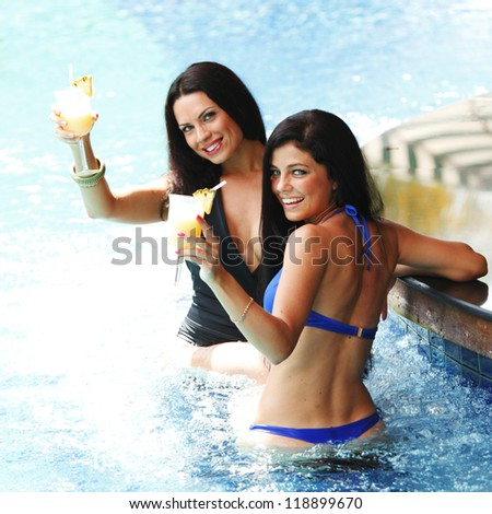 Two beautiful women relaxing in swimming pool with cocktails