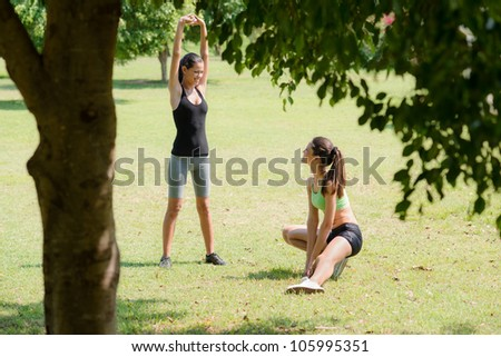 Two beautiful women stretching in city park after running and sport activity