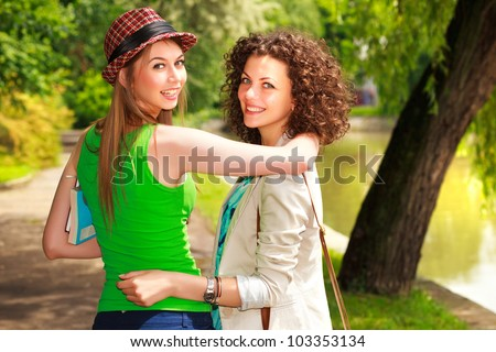 Two beautiful women walking and smiling in the park by the river - sunny day