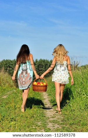 Two beautiful women walking at the meadow with basket with apples.