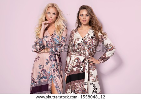 Photo of  Two beautiful women wearing nice long dresses. Portrait of happy smiling girls in stylish glamorous clothes. Autumn spring fashion photo on pink background.