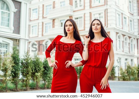 Two beautiful young brunette girls in a red dress posing on the street. Portrait of sisters models.