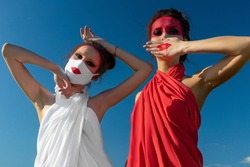 Two beautiful young brunette girls with creative bright makeup in tunics against a blue sky. One girl in a mask, the other girl closes her mouth with her hand.