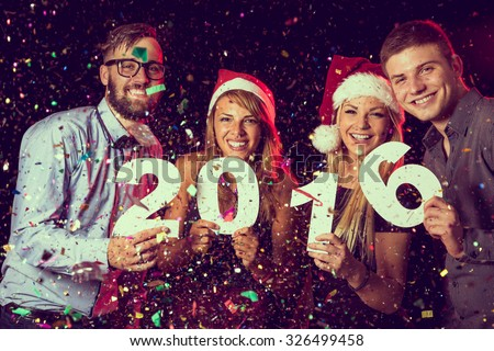Two beautiful young couples having fun at New Year's Eve Party, holding cardboard numbers 2016
