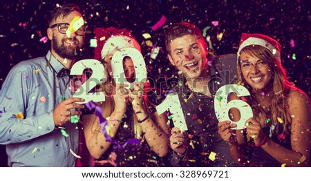 Two beautiful young couples having fun at New Year\'s Eve Party, holding cardboard numbers 2016