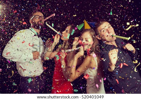 Two beautiful young couples having fun at New Year\'s party, wearing party hats, dancing and blowing party whistles. Focus on the couple on the right