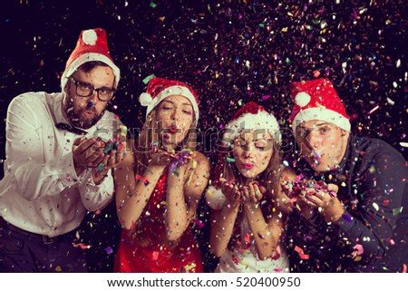 Two beautiful young couples wearing Santa\'s hats, blowing colorful confetti at midnight at New Year\'s Eve party