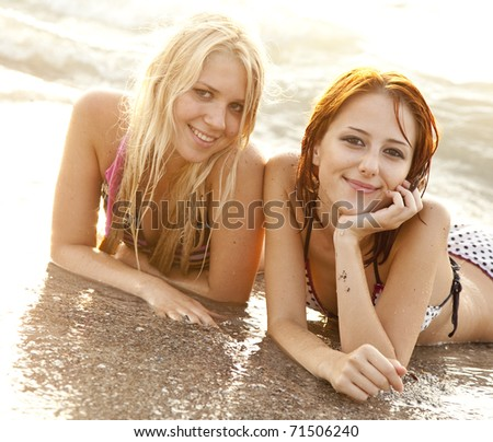 Two beautiful young girlfriends in bikini on the beach at sunrise. Photo with counter-light on background.