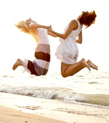 Two beautiful young girlfriends jumping on the beach at sunset. Photo with counter-light on background.