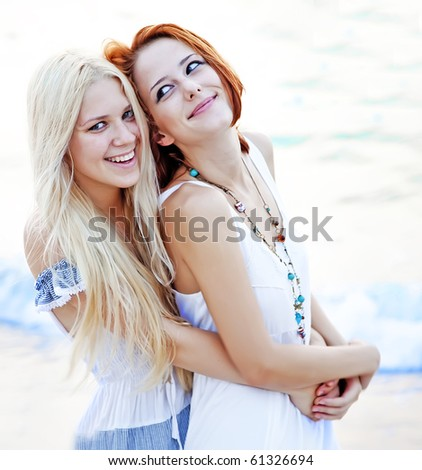 Two beautiful young girlfriends on the beach at sunset. Photo with counter-light on background.