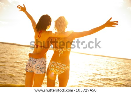 two beautiful young girlfriends opened her hands with delight at the blue sea and sky