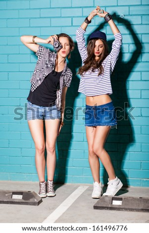 two beautiful young girls dance, take pictures and have fun at parking lot