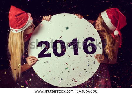 Two beautiful young girls enjoying at New Year\'s Eve party, holding cardboard circle with 2016 written on it